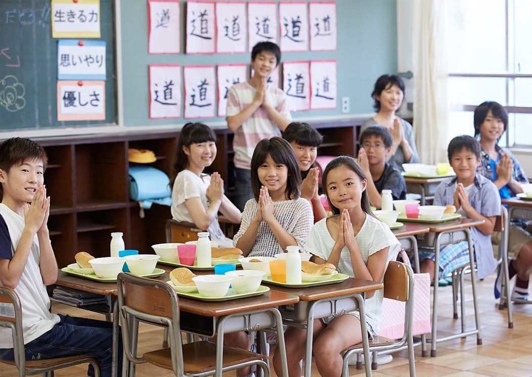 学校給食の前で手を合わせている小学生たちの写真